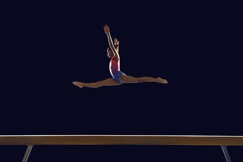 gymnaste qui saute au dessus de la poutre