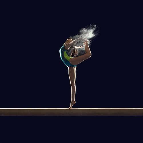 gymnaste sur la poutre qui lance de la poudre